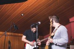 Due tipi che giocano la chitarra elettrica e che cantano fotografie stock