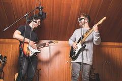 Due tipi che giocano la chitarra elettrica e che cantano immagine stock