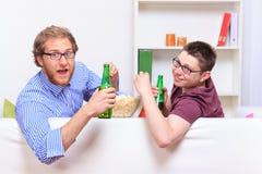 Due tipi con birra e popcorn sul sofà fotografia stock libera da diritti