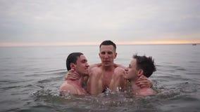Due tipi gettano un terzo sopra l'acqua e fa una vibrazione e si tuffa video d archivio