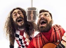 Due tipi nerd che cantano insieme immagini stock