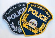 Due toppe della polizia delle colline di Braddock, una nera ed oro e l'altro sottomesso su un fondo bianco fotografia stock libera da diritti