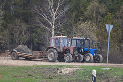 Due trattori alla campagna - macchinario per agricoltura Immagini Stock