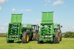 Due trattori verdi di John Deere che tirano gli spanditori di stallatico bunning Immagini Stock Libere da Diritti