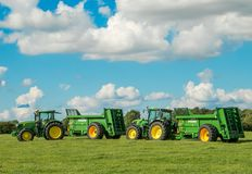 Due trattori verdi di John Deere che tirano gli spanditori di stallatico bunning Immagine Stock