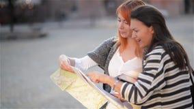 Due turisti attraenti della donna che viaggiano in vacanza nel sorridere della città felice Ragazze con la mappa della città alla video d archivio