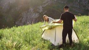Due turisti hanno installato una tenda contro il contesto delle montagne stock footage