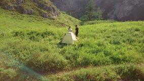 Due turisti si rilassano vicino ad una tenda nelle montagne stock footage