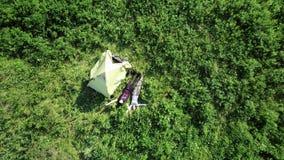 Due turisti si rilassano vicino ad una tenda nelle montagne video d archivio