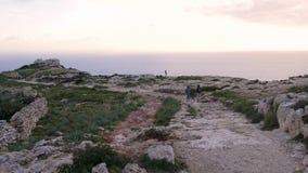 Due turisti vanno al bordo della scogliera osservare il mare, il tramonto e la natura stupefacente Superficie rocciosa stock footage