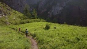 Due turisti vanno lungo il percorso in salita Vista da sopra video d archivio