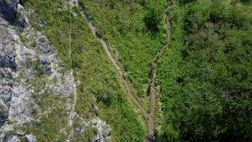 Due turisti vanno lungo il percorso in salita Vista da sopra stock footage