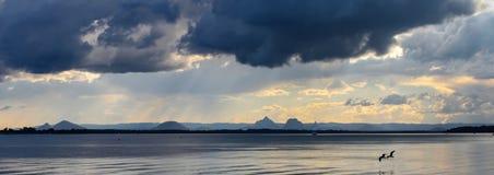 Due uccelli sorvolano insieme l'acqua sotto le nuvole scure minacciose con il sole dorato che attraversa e piovono sulle montagne immagini stock libere da diritti