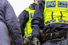 Due ufficiali di polizia in una folla, fine su dell'ente superiore con la maglia Immagini Stock Libere da Diritti