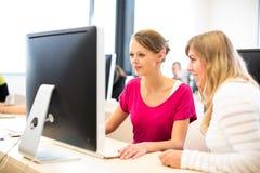 Due universtiy/studenti di college femminili che lavorano ai comp. del desktop Immagine Stock