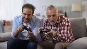 Due uomini adulti che vincono dare del video gioco alto--cinque, celebrando vittoria, svago stock footage