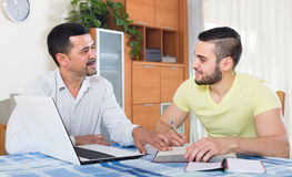 Due uomini adulti con il computer portatile all'interno Immagini Stock