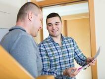 Due uomini al gradino della porta dell'appartamento immagini stock