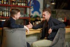 Due uomini allegri degli amici si siedono in una barra alla barra e parlano di qualcosa che ridono Fotografie Stock