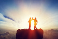 Due uomini, amici alti cinque sopra le montagne accordo Immagini Stock
