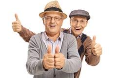 Due uomini anziani allegri che tengono i loro pollici su Fotografia Stock