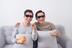 Due uomini asiatici in vetri 3d che si siedono sul sofà e sul film di sorveglianza Fotografie Stock Libere da Diritti