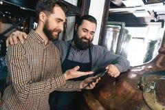 Due uomini barbuti adulti contano sullo scorrimento dell'acqua della compressa per fare brewery Elaborazione della birra fotografia stock