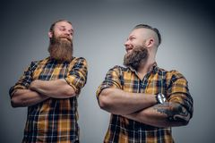 Due uomini barbuti divertenti si sono vestiti in una camicia di plaid che posa sulle sedere grige Fotografie Stock Libere da Diritti