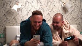 Due uomini barbuti sul letto nello sguardo dell'accappatoio in telefono e molto sorpreso Movimento lento stock footage