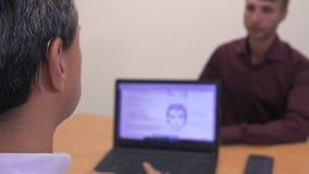 Due uomini bei ad una tavola davanti ad un computer portatile video d archivio