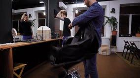 Due uomini bei in parrucchiere moderno stanno discutendo il hairstyling futuro Barbiere professionista vestito in abbigliamento c archivi video