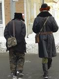 Due uomini che camminano giù la via in un vecchio abbigliamento rivoluzionario, retro stile Inverno, Russia fotografie stock