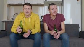 Due uomini che collocano sullo strato e guardare una partita di calcio sulla TV, sulla birra della bevanda e sul commento video d archivio