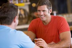 Due uomini che comunicano sopra la birra in una barra Immagini Stock Libere da Diritti