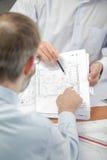 Due uomini che esaminano i piani dentro Fotografie Stock Libere da Diritti