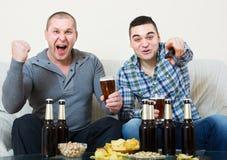Due uomini che guardano calcio con birra dell'interno Immagini Stock