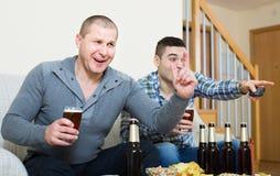 Due uomini che guardano calcio con birra dell'interno Fotografia Stock