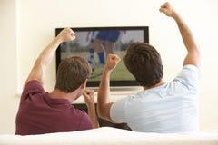 Due uomini che guardano TV a grande schermo a casa Immagine Stock Libera da Diritti