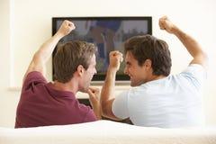 Due uomini che guardano TV a grande schermo a casa Immagini Stock Libere da Diritti