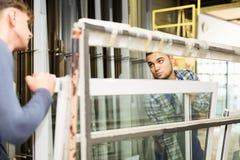 Due uomini che ispezionano le finestre Immagine Stock