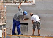 Due uomini che lavorano a costruire una casa, facciata di cemento bianco Fotografia Stock Libera da Diritti
