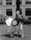 Due uomini che lottano con un orologio da tasca surdimensionato (tutte le persone rappresentate non sono vivente più lungo e ness Fotografia Stock Libera da Diritti