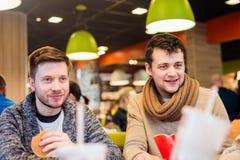 Due uomini che mangiano fuori nel fast food, parlante immagini stock
