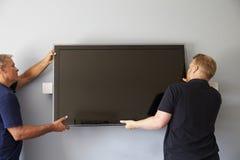 Due uomini che misura la televisione dello schermo piano per murare fotografia stock