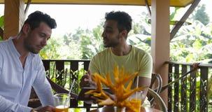 Due uomini che per mezzo del computer della compressa che si siede sul terrazzo che parla insieme, web praticante il surfing di e archivi video