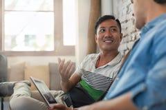 Due uomini che per mezzo del computer portatile al caffè, amici multietnici Immagini Stock Libere da Diritti
