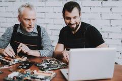 Due uomini che riparano l'attrezzatura dell'hardware dal PC fotografie stock libere da diritti