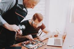 Due uomini che riparano l'attrezzatura dell'hardware in officina immagine stock libera da diritti