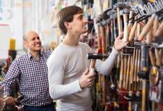 Due uomini che scelgono martellano la sezione di foggiatura fotografia stock libera da diritti