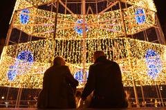 Due uomini che si siedono davanti al trre di natale fatto di luce Fotografie Stock